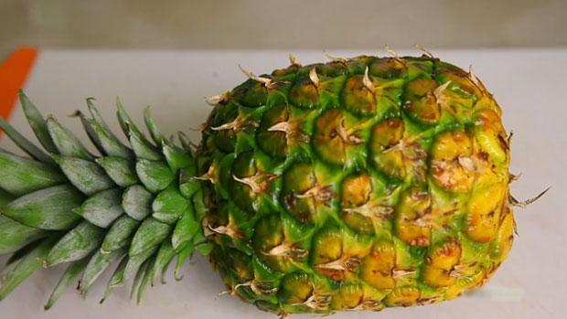 Положите ананас на бок