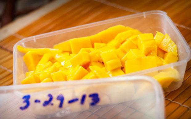 Поместите кусочки манго в контейнеры для замораживания.