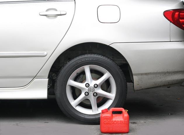 Установите канистру на землю возле машины с открытым баком.