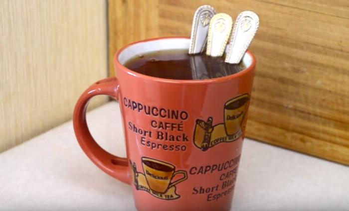кружка с чаем и тремя чайными ложками