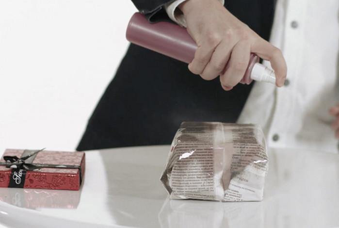 мужчина распыляет лак на газету