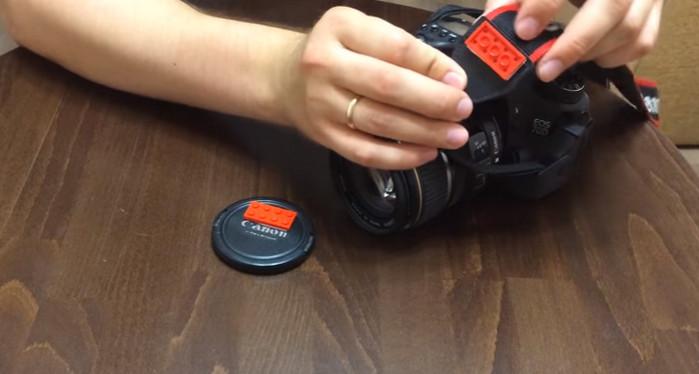 к крышке фотоаппарата прикреплен кубик лего