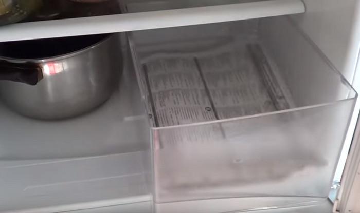 застеленный газетой ящик в холодильнике
