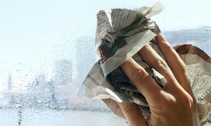 человек моет окна газетами