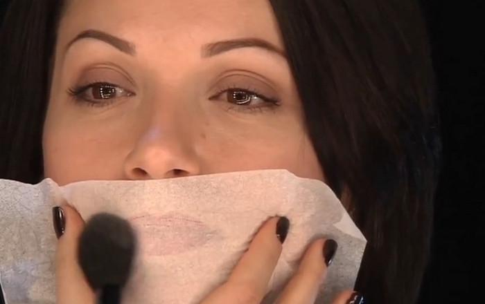 девушка пудрит губы через салфетку