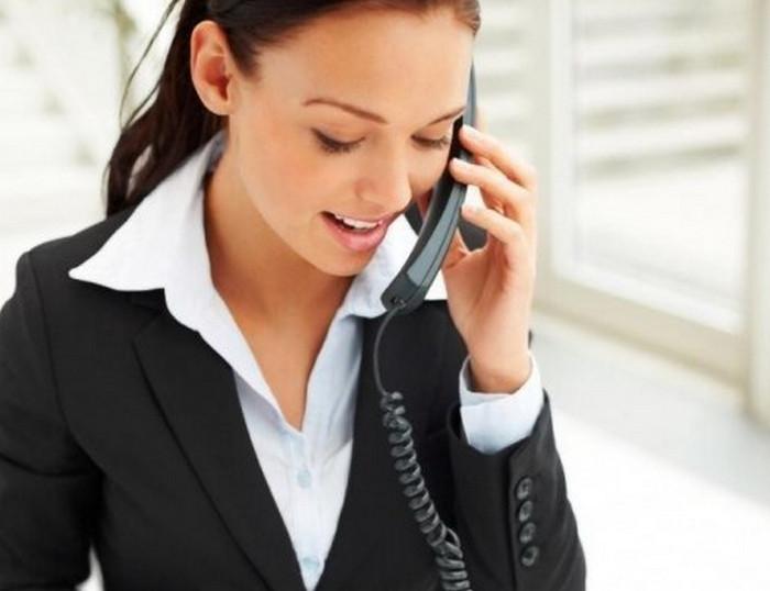 офисный сотрудник улыбается при разговоре по телефону