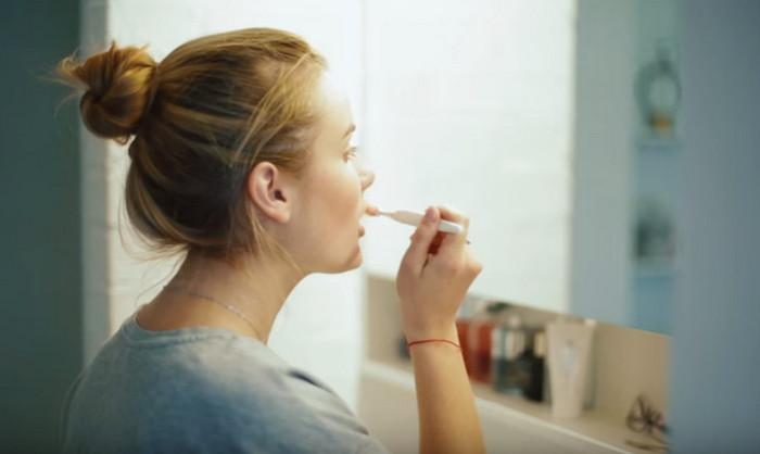 девушка массирует губы зубной щеткой