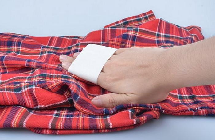 человек чистит одежду скотчем