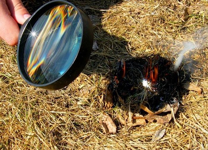 разжигает лупой костер