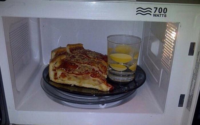 пицца и стакан с водой в микроволновке