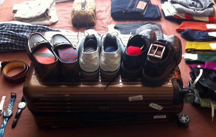 три пары обуви на чемодане