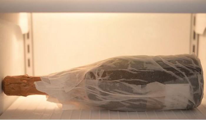 обернутая влажным полотенцем бутылка в морозильной камере