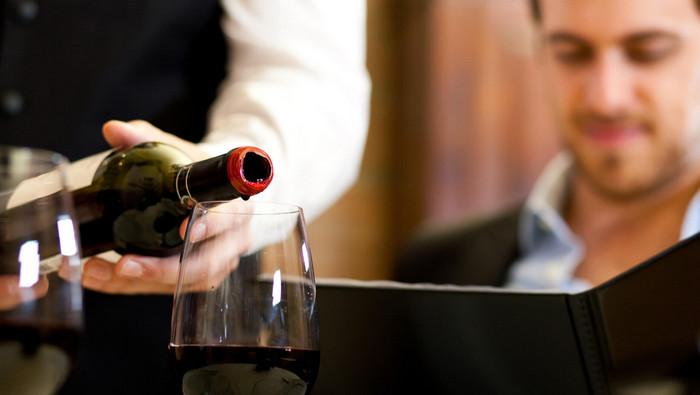 официант наливает вино