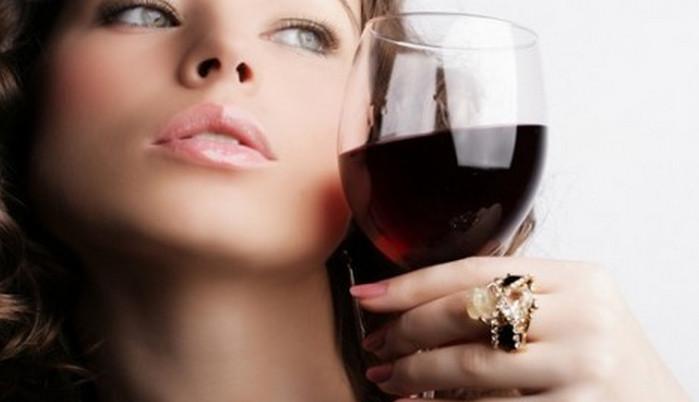 девушка держит бокал вина у лица