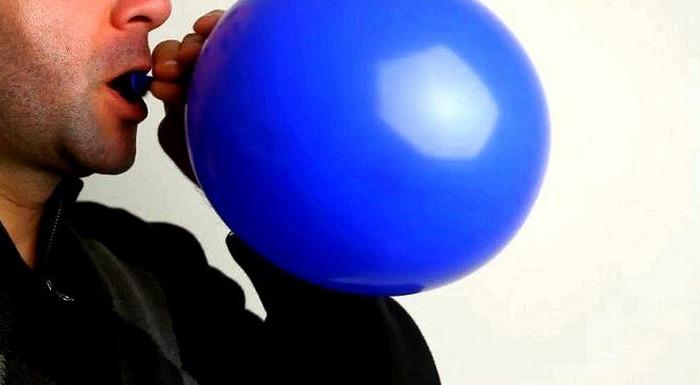 человек надувает воздушный шар