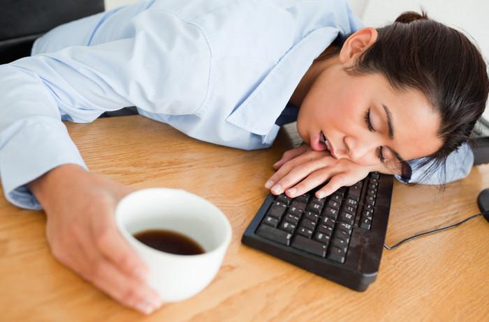 девушка спит на рабочем столе возле кофе