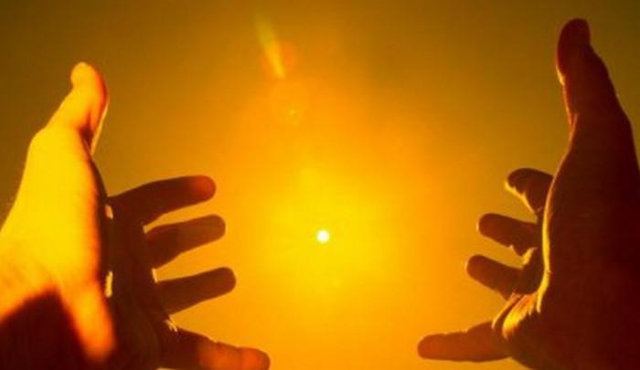 человек тянет руки к солнцу