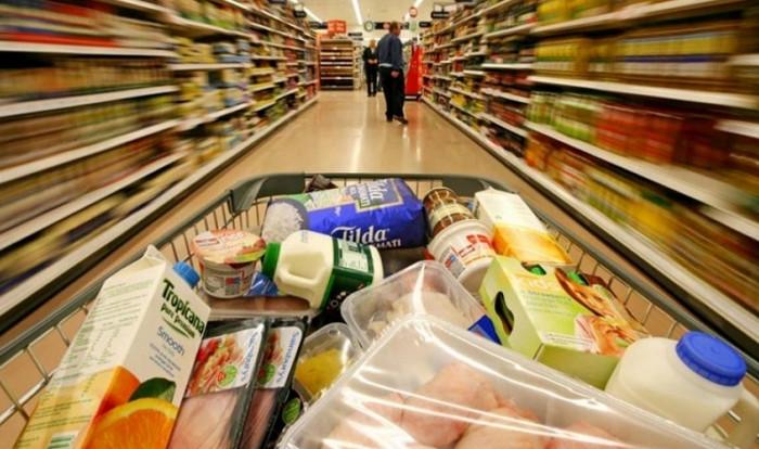 человек идет с тележкой по супермаркету