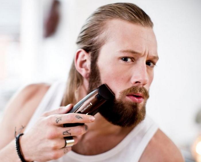 мужчина бреет бороду триммером