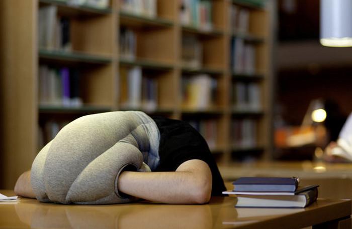 человек лежит на подушке за рабочим столом