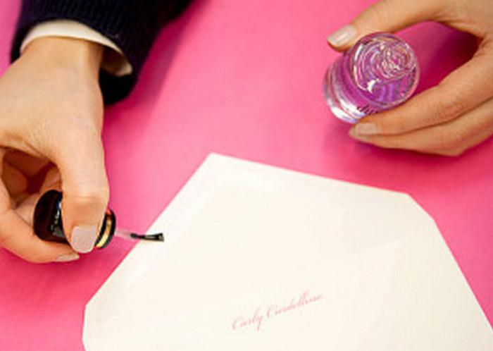 девушка заклеивает конверт лаком для ногтей