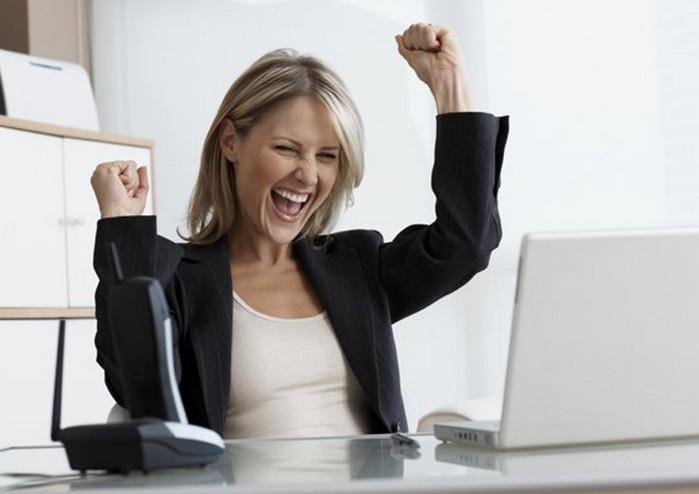 довольная девушка за ноутбуком в офисе