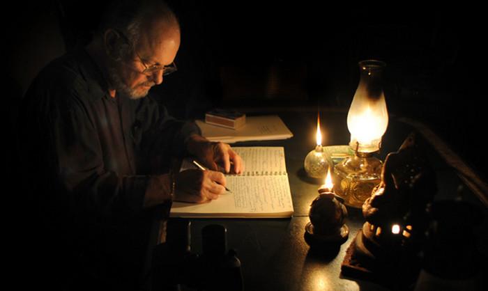 писатель пишет при зажженной свече