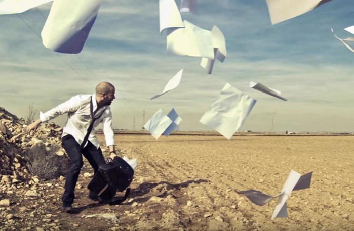 человек разбрасывает исписанную бумагу в поле