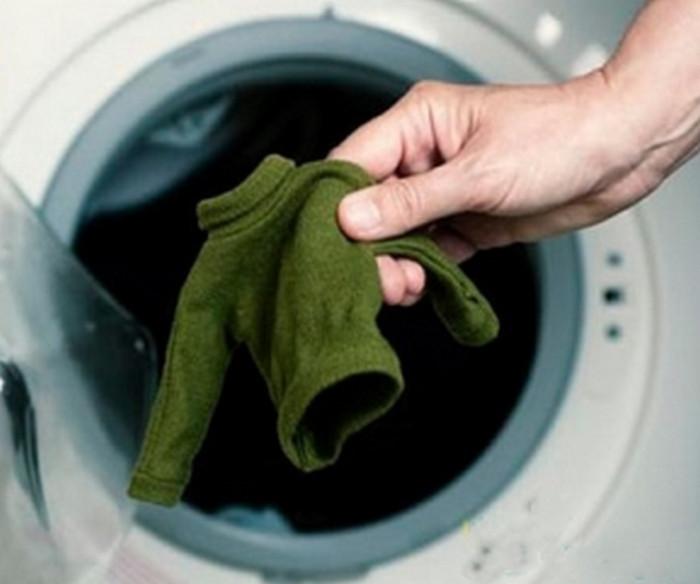 человек достает севший свитер из стиралки