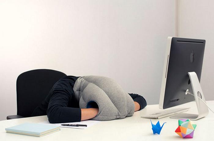 человек спит за столом в подушке-страусе
