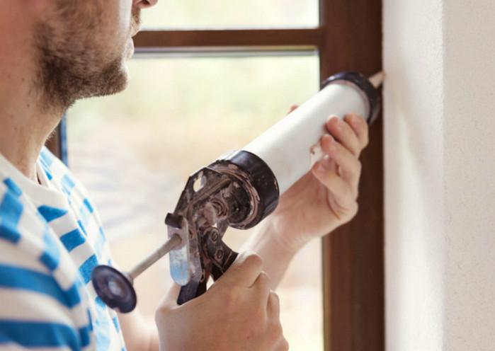 мужчина с герметиком возле окна