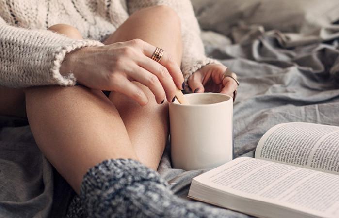 девушка пьет кофе и читает книгу