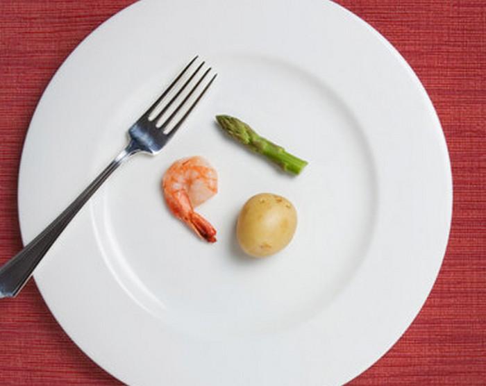 креветка и кусочек спаржи на тарелке