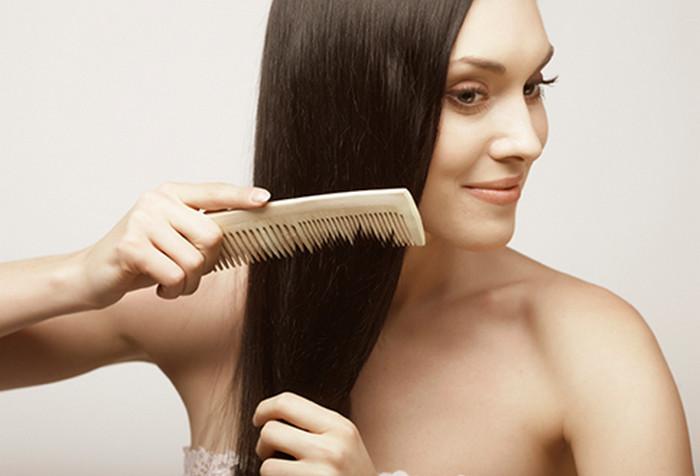 девушка расчесывает деревянным гребнем волосы