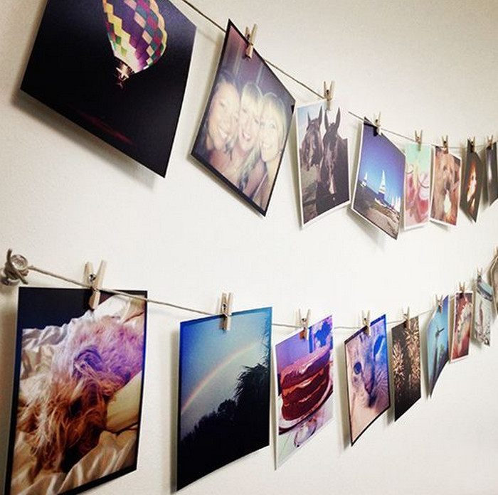 фотографии на веревках у стены