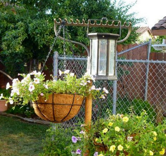 висящий на граблях в саду фонарь