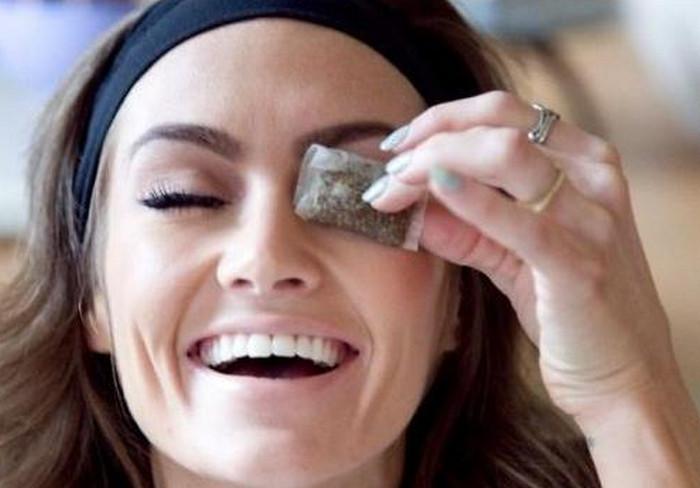 девушка прикладывает пакетики чая к глазам