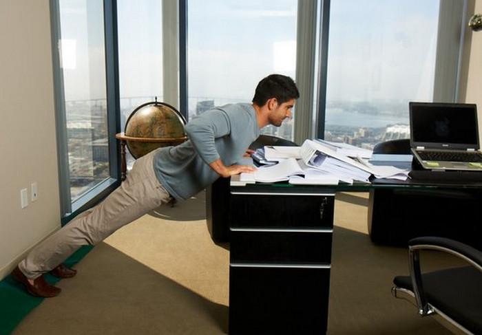 мужчина занимается фитнесом в офисе