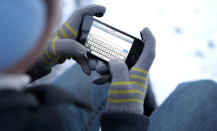человек в перчатках пользуется смартфоном на улице