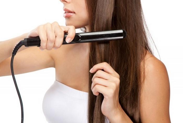 девушка выпрямляет волосы утюжками