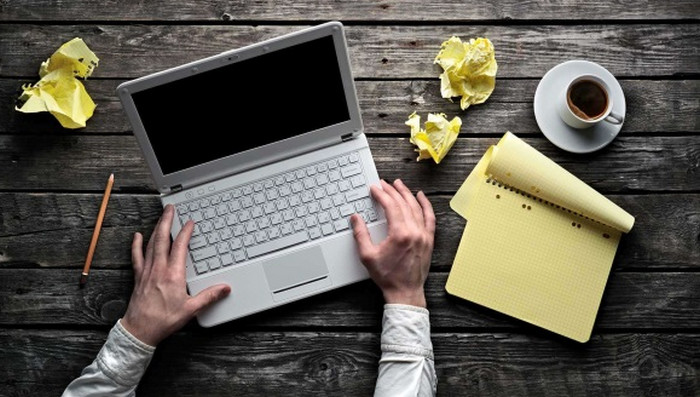человек за ноутбуком пишет текст