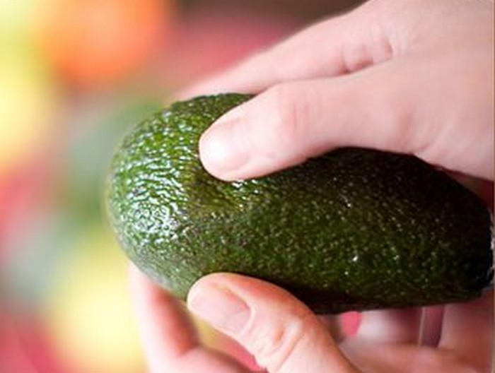 человек надавливает авокадо