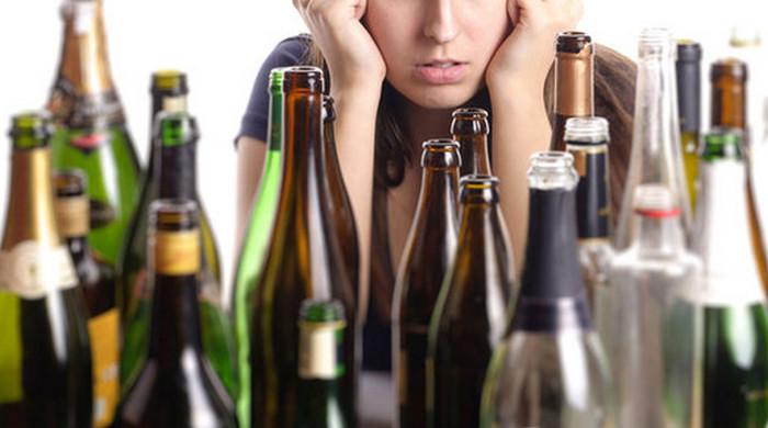 девушка сидит перед пустыми бутылками
