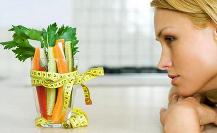 девушка уныло смотрит на овощи