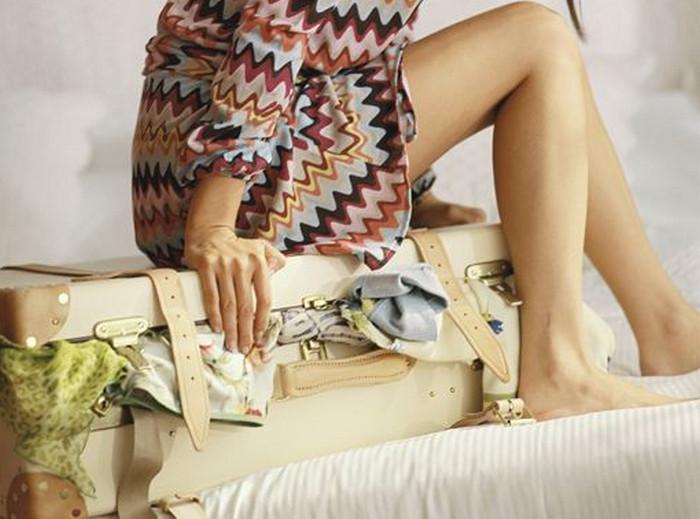 девушка сидит на чемодане