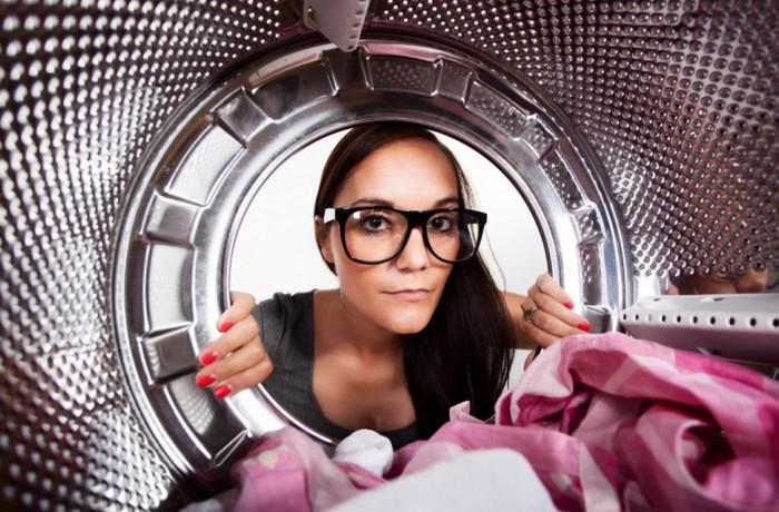 девушка заглядывает в стиральную машину