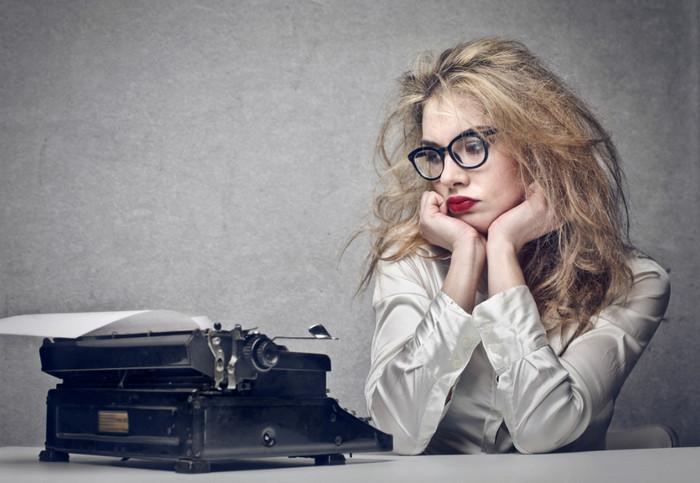 девушка сидит рядом с пишущей машинкой