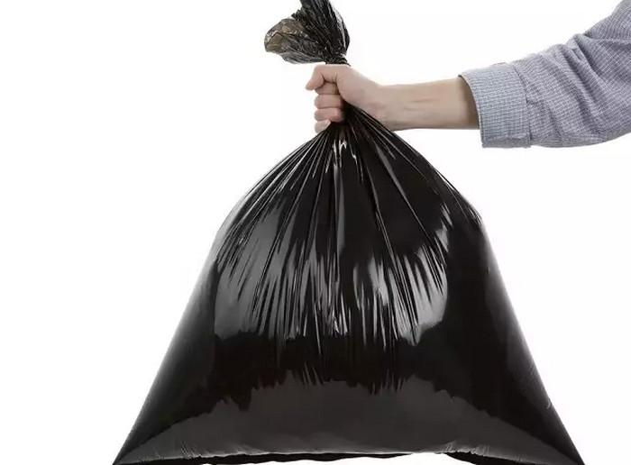 человек держит пакет с мусором