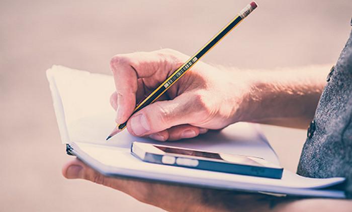 человек пишет в тетради
