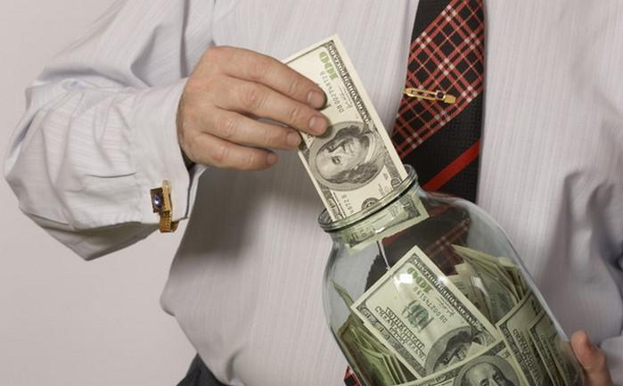 мужчина кладет деньги в банку